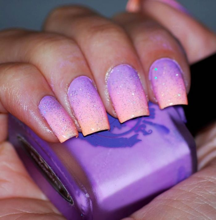 purple to pink and orange glitter gradient nail polish, red ombre nails, medium length square nails, hand holding nail polish bottle