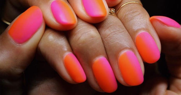 orange to pink vertical gradient matte nail polish, short squoval nails, golden rings on the fingers, french tip acrylic nails