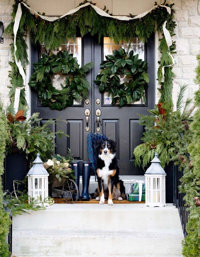 large outdoor christmas decorations, wreaths hanging on the door and door frame, dog standing on the stairs