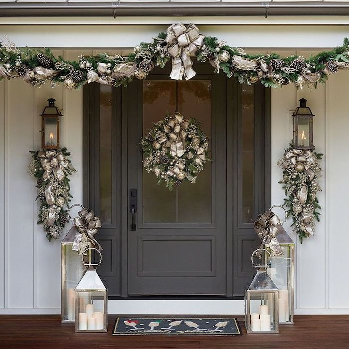 wreaths decorated with gold ribbons, hanging over door and door frame, christmas deer decorations, lanterns on both sides