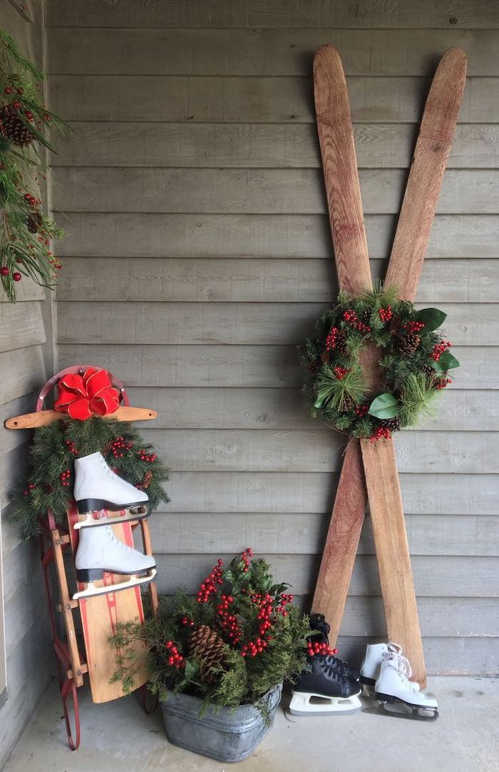 wooden skis decorated with wreath, wooden sled with ice skating shoes, grinch outdoor christmas decorations, arranged on front porch