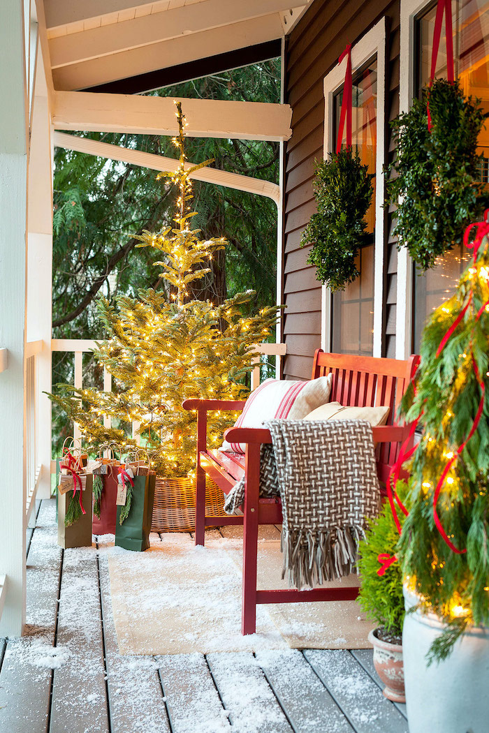 tree decorated with lights, placed on the front porch, next to a wooden bench, large outdoor christmas decorations