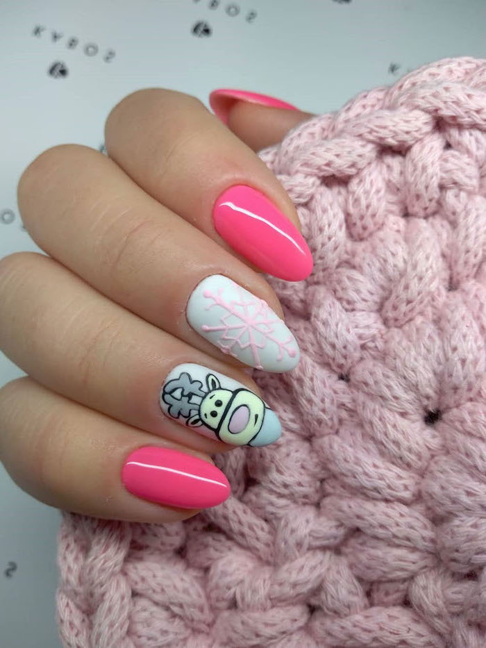 pink and white nail polish, reindeer decoration on ring finger, snowflake decoration on middle finger, nude nail designs