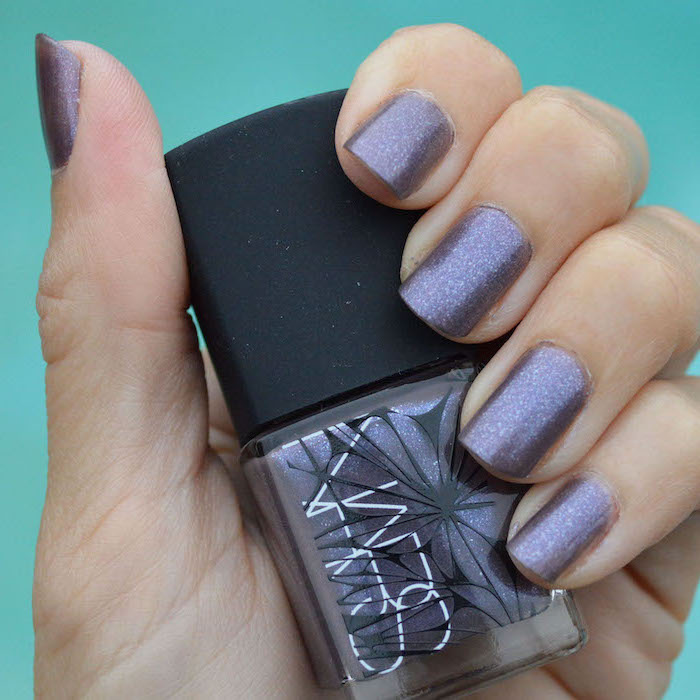hand holding a nail polish bottle, popular nail colors, purple glitter nail polish, short squoval nails