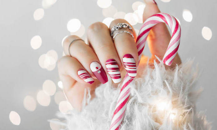 red and white nail polish, candy cane decorations on each nail, christmas nail colors, hand holding a candy cane