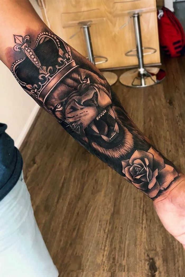 roaring lion with crown on its head, rose underneath it on the wrist, forearm tattoo, lion tattoos for females