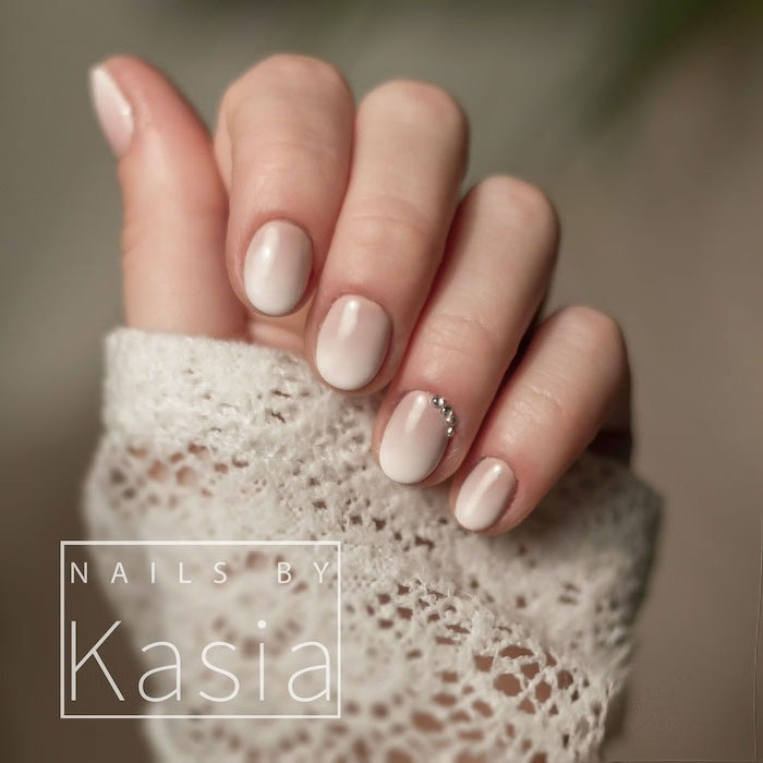 short squoval nails, nude to white gradient nail polish, rhinestones decorations on the ring finger, french ombre nails