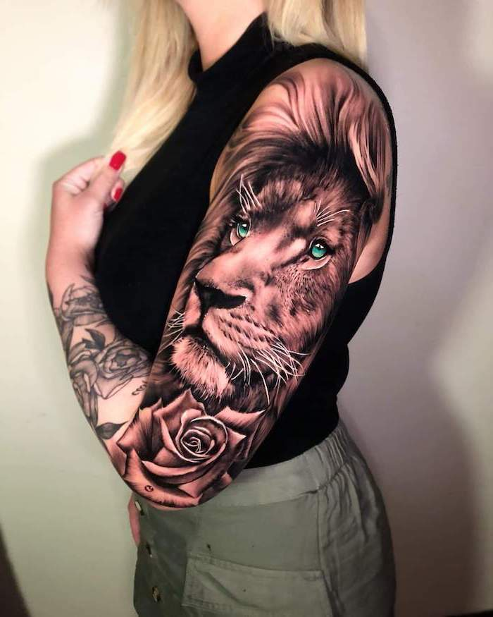 sleeve tattoo, on woman with blonde hair, wearing khaki pants and black top, lion with crown tattoo, lion head with blue eyes