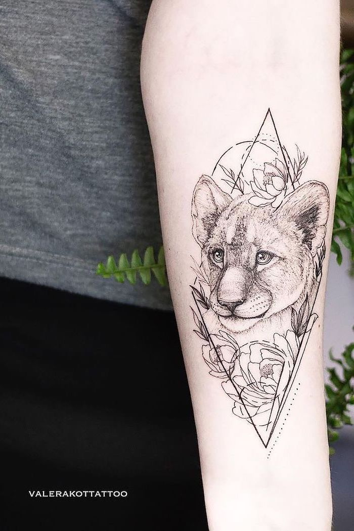 small lion cub tattoo, forearm tattoo, surrounded by flowers, lion tattoos for females, geometrical design