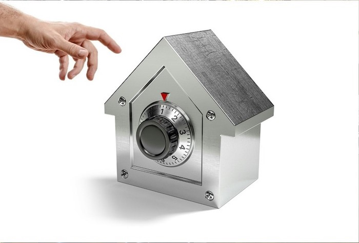steel safe in the shape of a house, target for burglars, placed on white surface