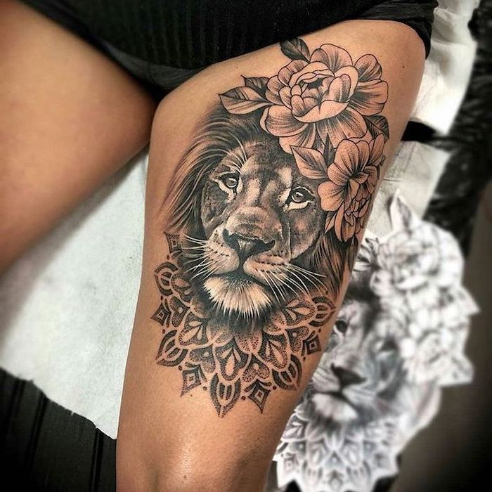 lion head, surrounded by flowers, mandala tattoo, lion thigh tattoo, on woman with black shorts