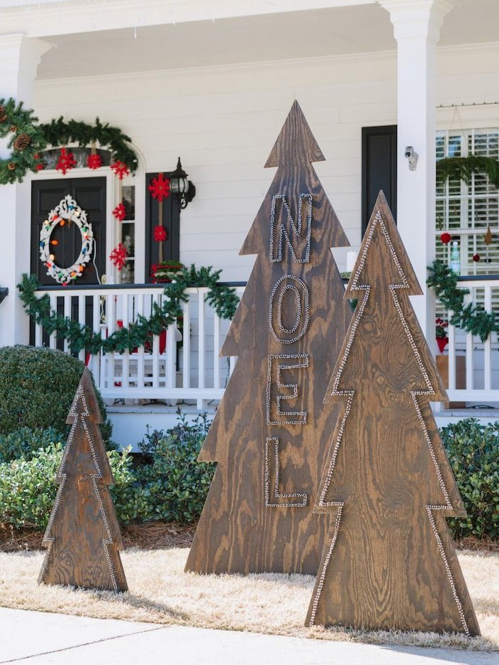 outdoor snowman decoration, three wooden boards in the shape of christmas trees, placed in front of the house