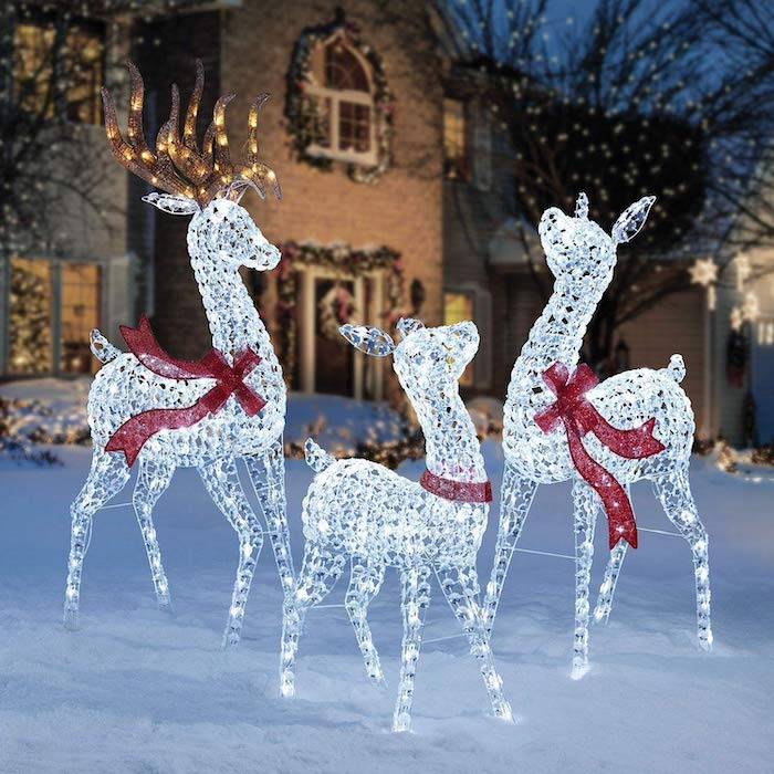 three reindeer figurines with lights, decorated with red ribbons, placed in the snow, outdoor snowman decoration