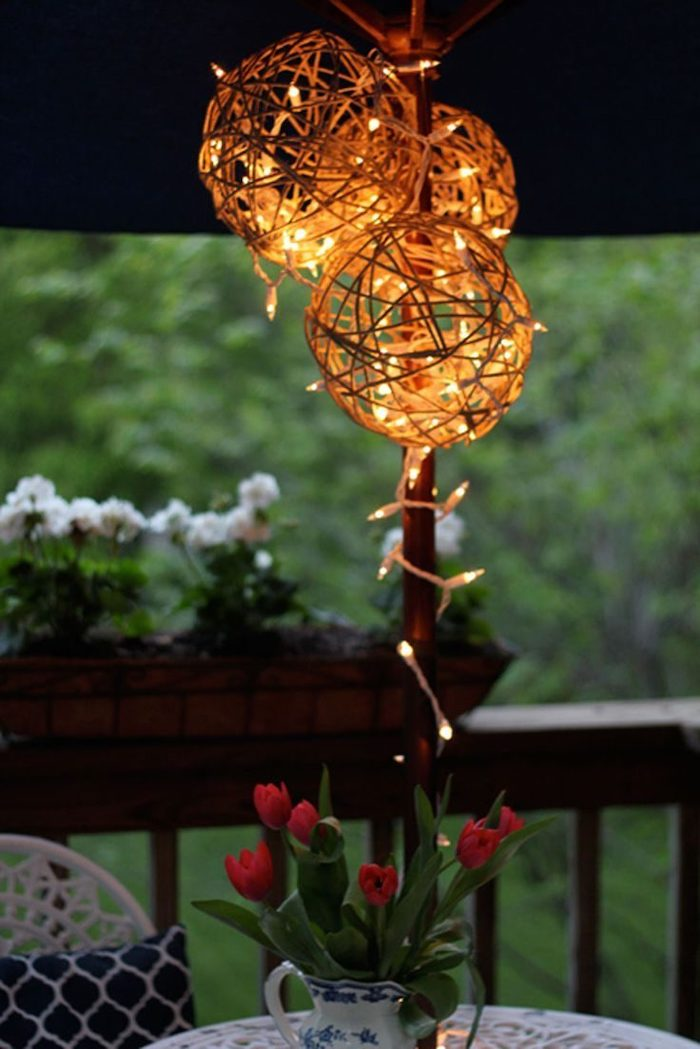 outdoor christmas decorations ideas, step by step diy tutorial, lanterns made of twine, hanging over a table, under an umbrella