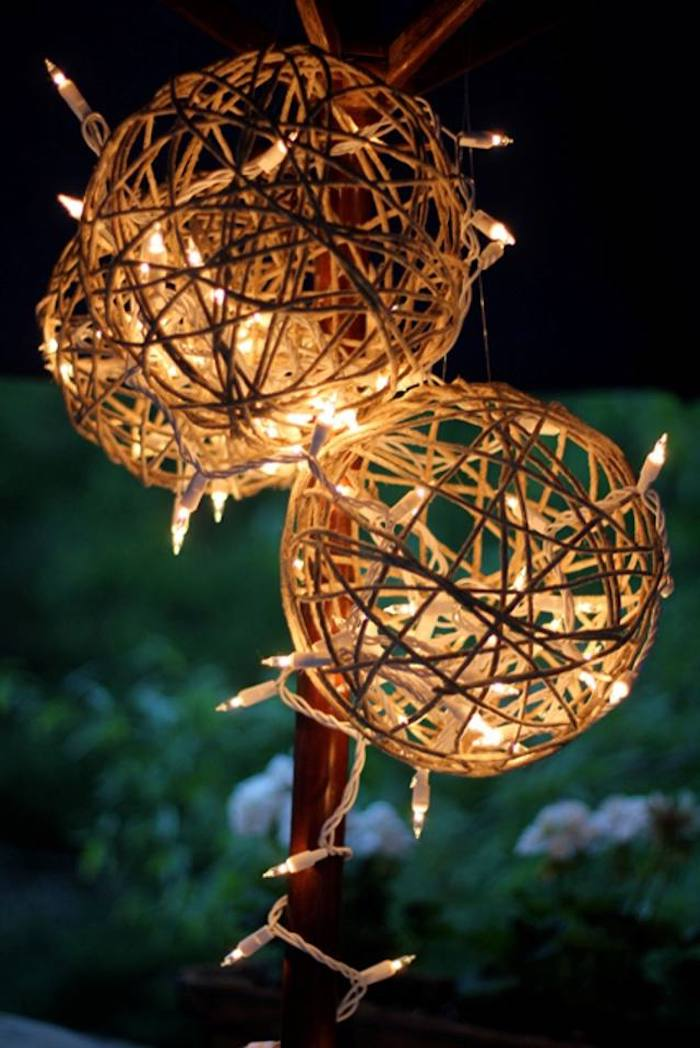three lanterns made of twine, lights intertwined in them, outdoor christmas decorations ideas, hanging under an umbrella