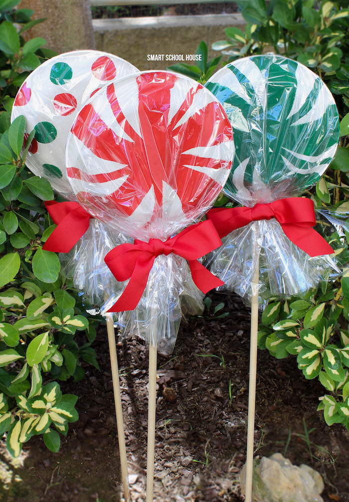 outdoor lighted christmas decorations, paper plate lollipops, decorations for your yard, wrapped with red ribbon