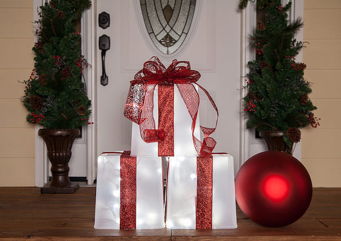yard decorations, presents made of plastic containers, lights inside, wrapped with red ribbons, placed on wooden porch