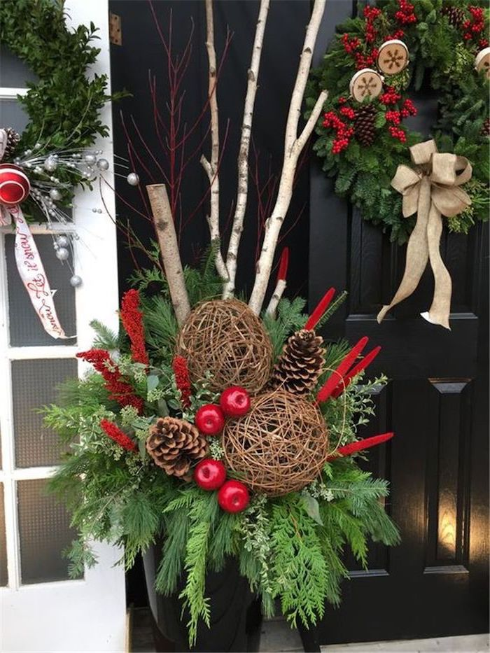 tree branches decorated with twine, pine cones and berries, outdoor snowman decoration, paced in front of a black door with wreath