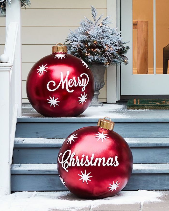 two large red baubles, merry christmas written on them, outdoor snowman decoration, placed on wooden staircase