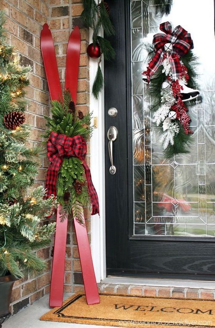 two red skis decorated with tree branches and plaid ribbon, outdoor snowman decoration, placed on the side of a door