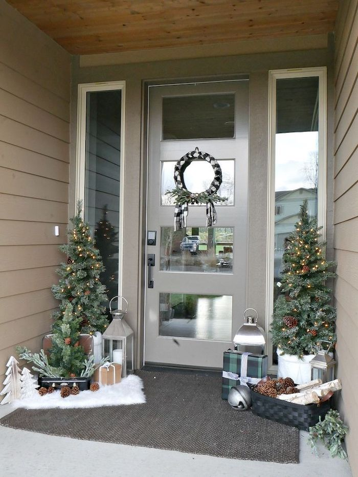 outside christmas decoration ideas, two trees with lights, placed on both sides of a door, decorated with wreath, made of black and white ribbons