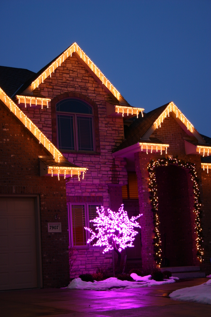 two storey house, decorated with lights, outside christmas decoration ideas, wreath with lights on the door frame, tree with pink lights