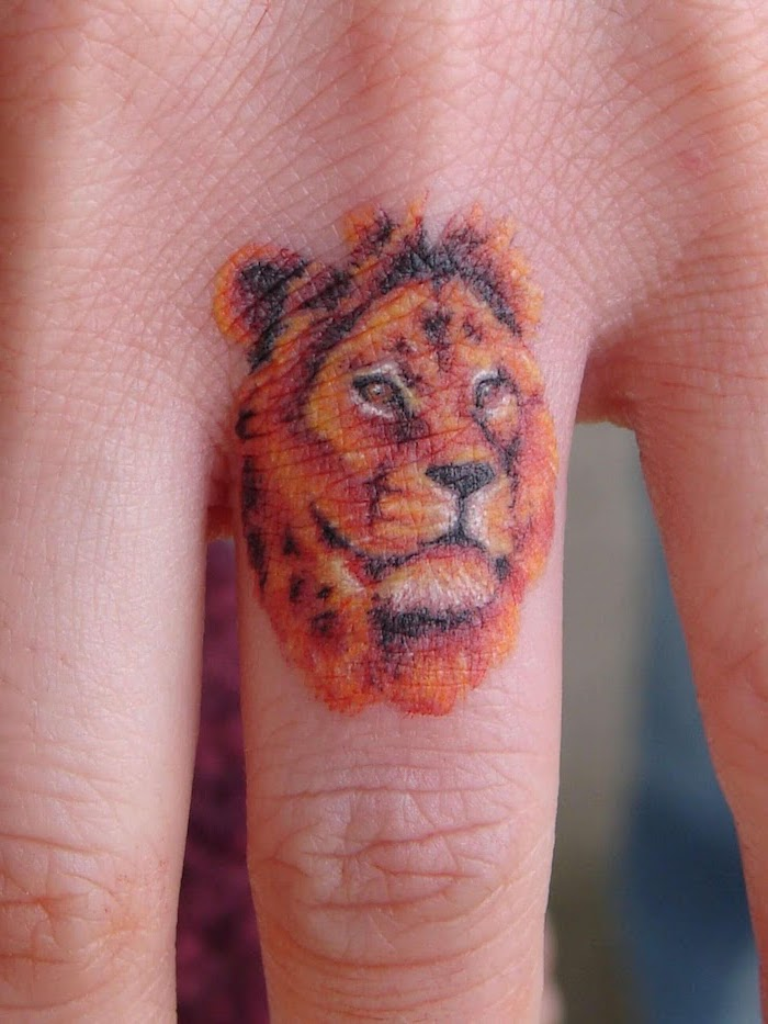finger tattoo on the ring finger, small lion tattoo, lion head in orange and black