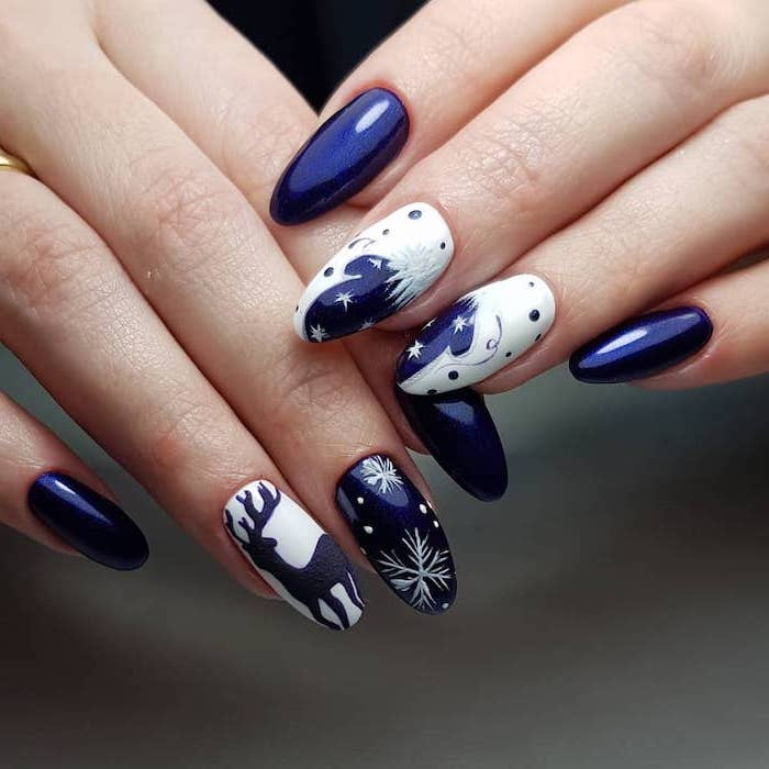 blue and white nail polish, snowflakes and reindeer decorations on middle and ring fingers, winter nail ideas