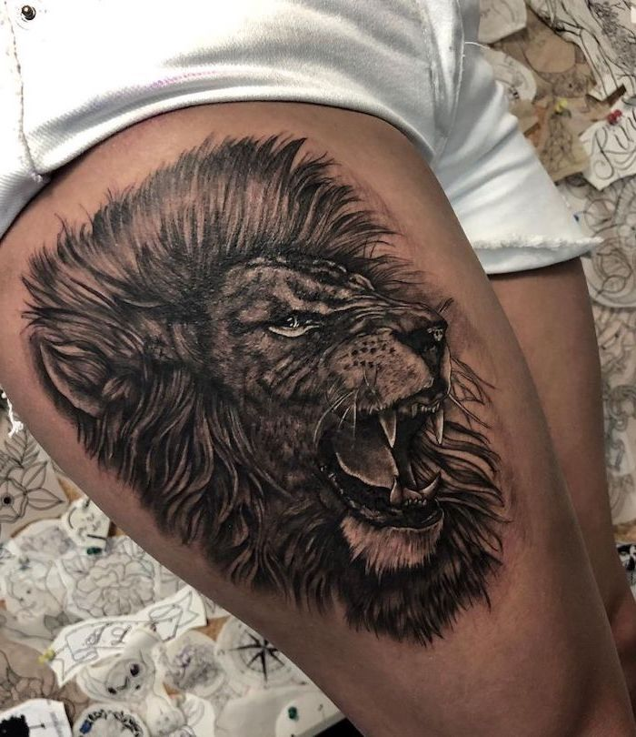 thigh tattoo, profile of a roaring line with large mane, on woman wearing white short jeans, small lion tattoo