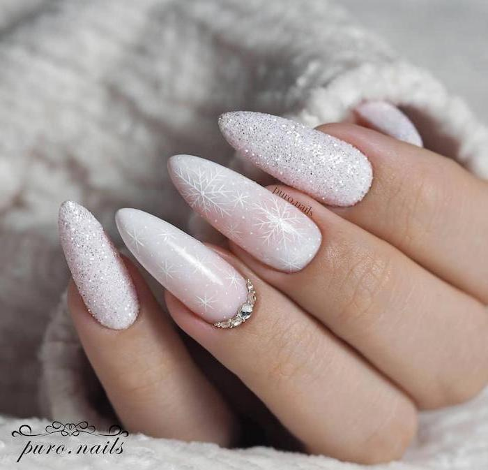white glitter nail polish, snowflakes and rhinestones decorations on the middle and ring finger, january nail colors, long stiletto nails