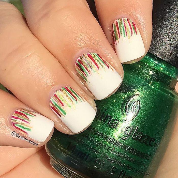 winter acrylic nails, hand holding nail polish bottle, white nail polish, red green and gold brush strokes