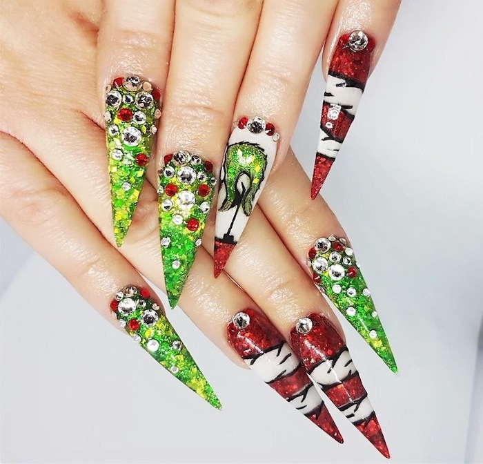 grinch themed decorations on each nail, winter acrylic nails, red and green glitter nail polish, decorations with rhinestones