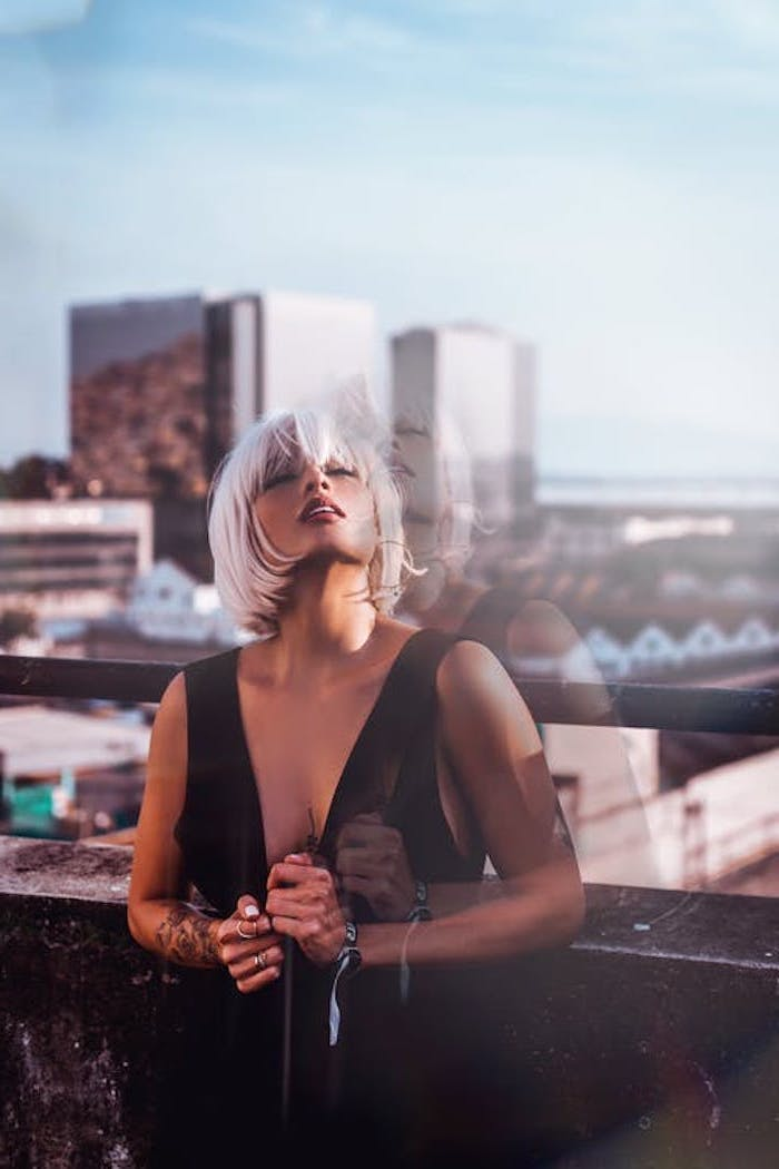 woman wearing black dress, hair color for short hair, standing on a balcony, short straight bob with bangs, ash grey hair
