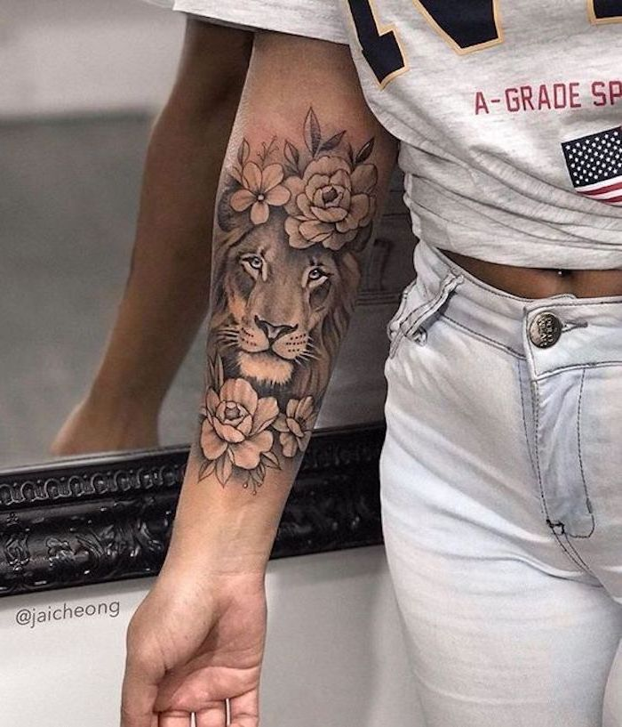 woman wearing white jeans and grey t shirt, small lion tattoo, forearm tattoo, lion head surrounded by flowers
