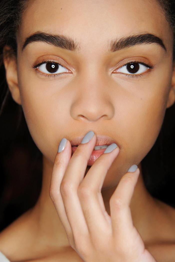woman with dark eyes and hair, grey nail polish, short squoval nails, cute winter nails