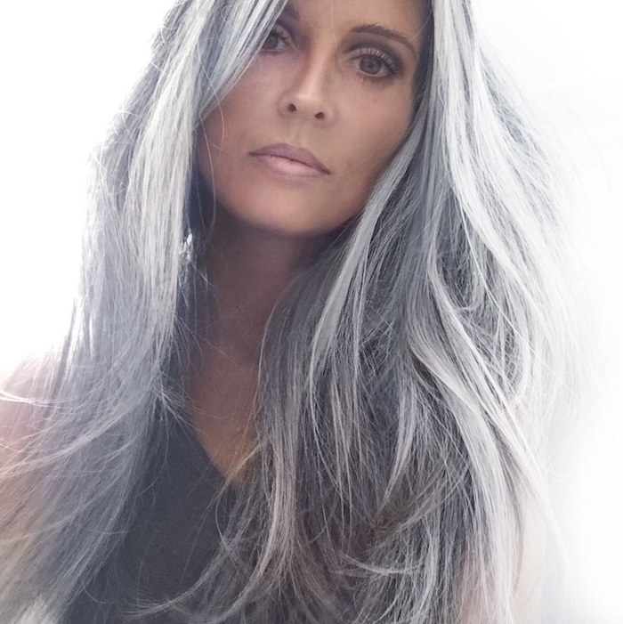 woman wearing black top, natural grey hair, long wavy hair, purple highlights in brown hair