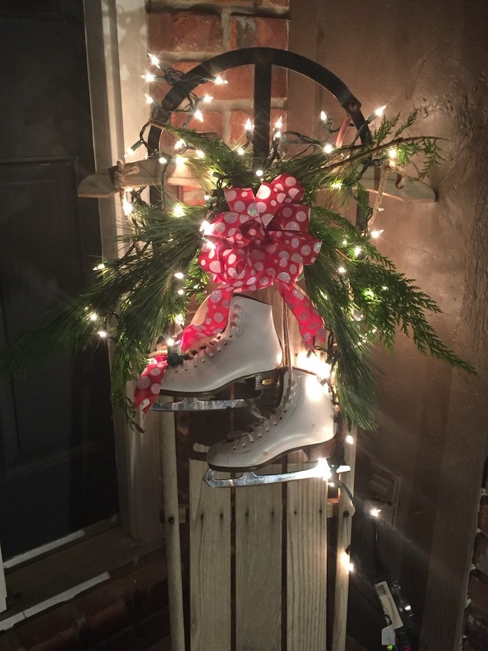 ice skating shoes on a sled, with tree branches and lights, placed on the porch, outside christmas decoration ideas