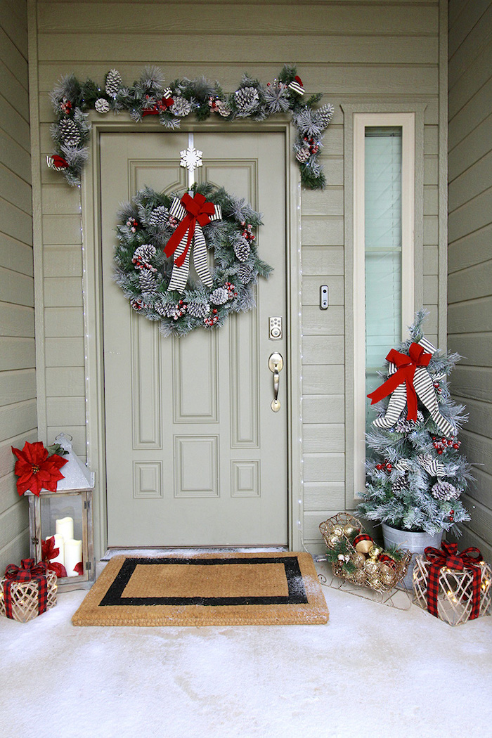 wreaths with pinecones, hanging on the door and door frame, large outdoor christmas decorations, decorated christmas tree in the corner