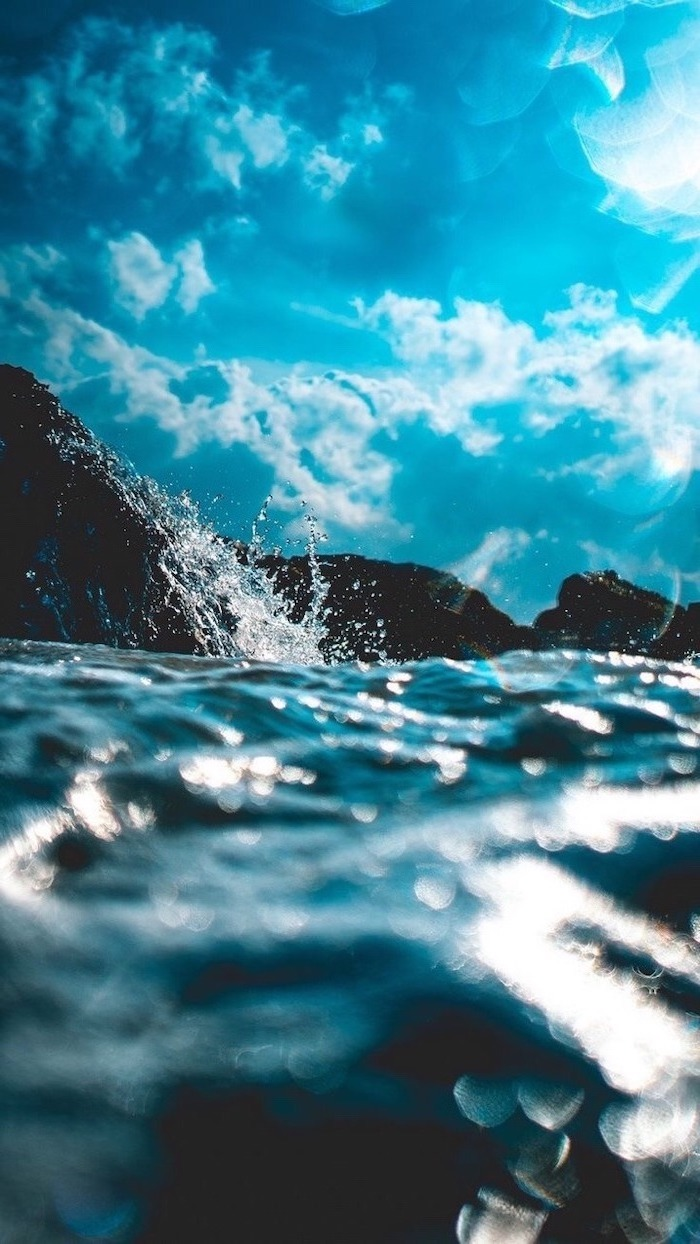 waves crashing into rocks, blue sky with white clouds above it, blue aesthetic background, beach landscape