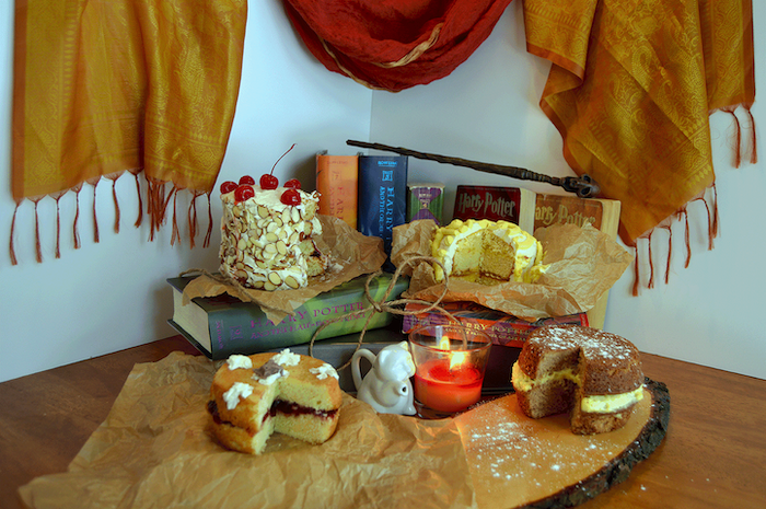 two hagrid's rock cakes, placed on wooden boards, harry potter cake ideas, harry potter books arranged behind them