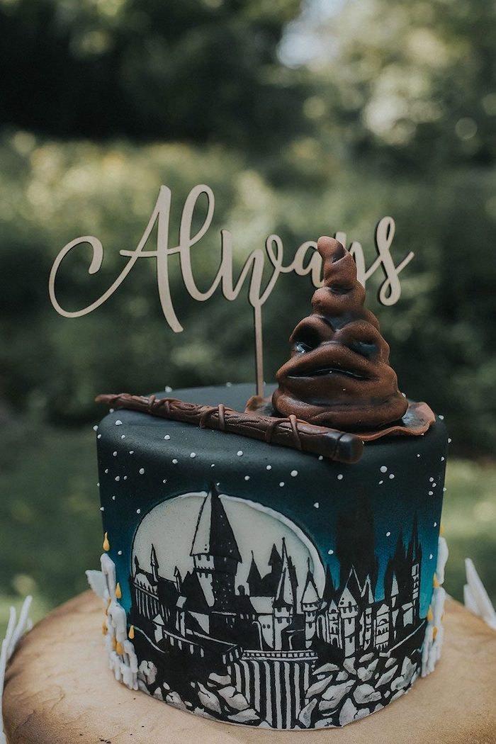 always topper, sorting hat and wand made of fondant, on top of black and blue cake, harry potter birthday cake, hogwarts drawn on it