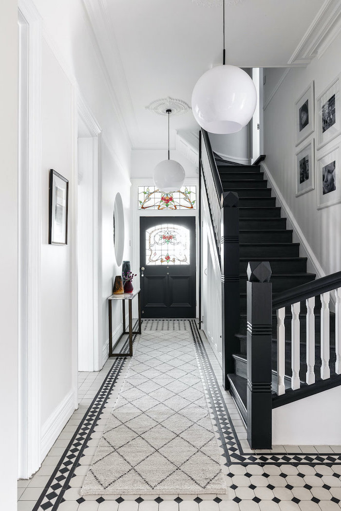 hallway with black and white tiled floor, stained glass windows, black door with windows, black staircase and white walls