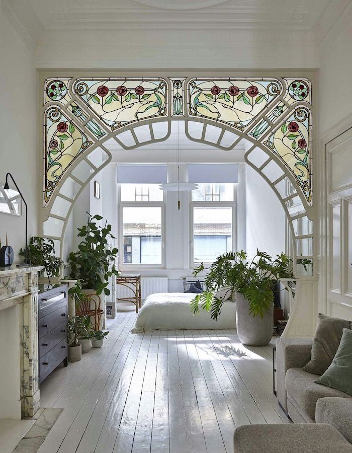 one bedroom flat with white walls, white wooden floor, leaded glass, arch made with stained glass, grey sofa with throw pillows