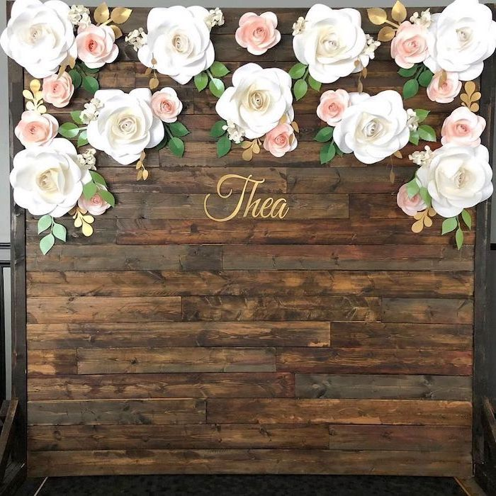 large backdrop made of wooden boards, paper flower templates, large white paper roses, arranged on the top