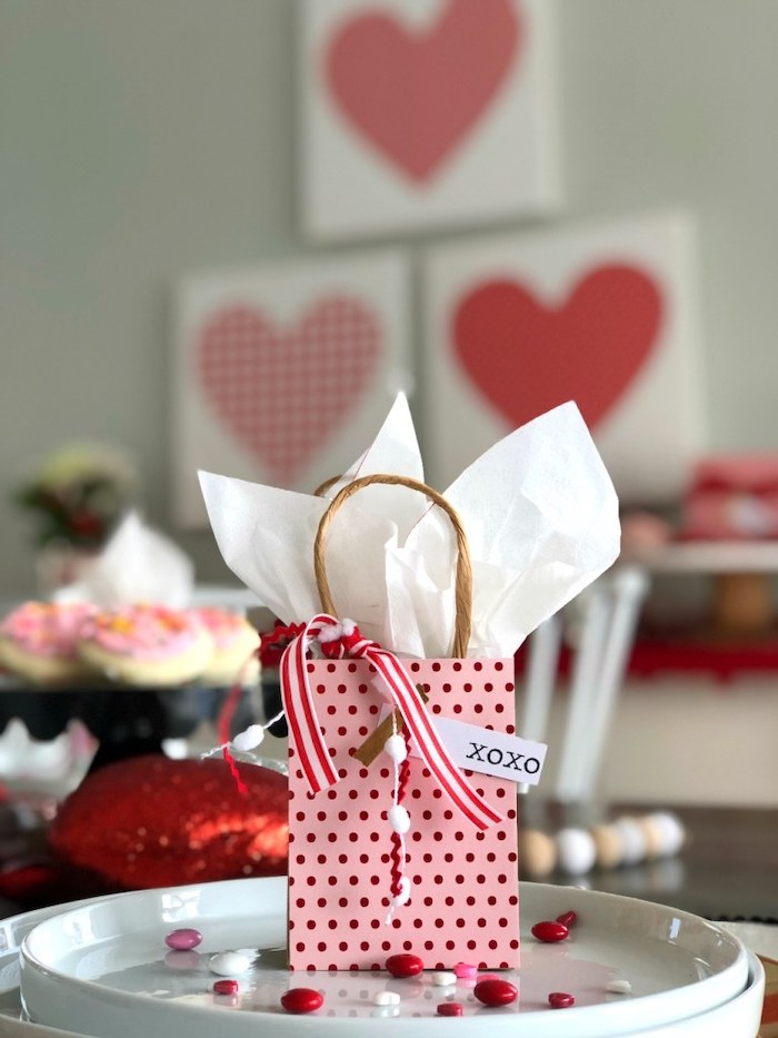small paper bag, filled with candy, placed on white plate, valentine decorations, red and white candy scattered on it