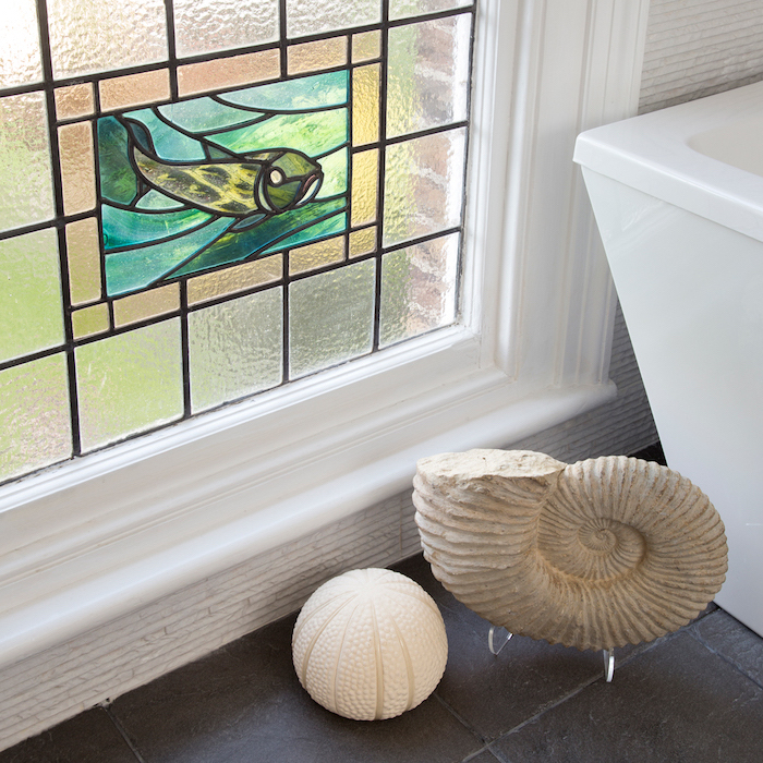 bathroom with black tiled floor, two ceramic figurines placed next to the window and bathtub, leaded glass
