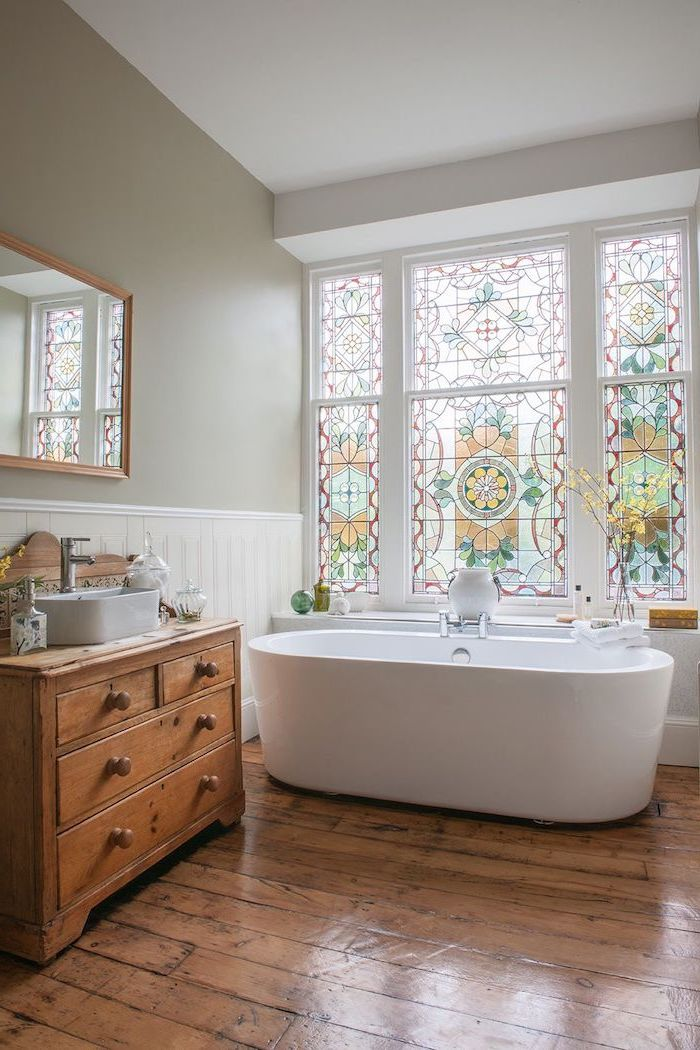 bathroom with wooden floors, bathtub under the window, stained glass windows, wooden cabinet under the sink