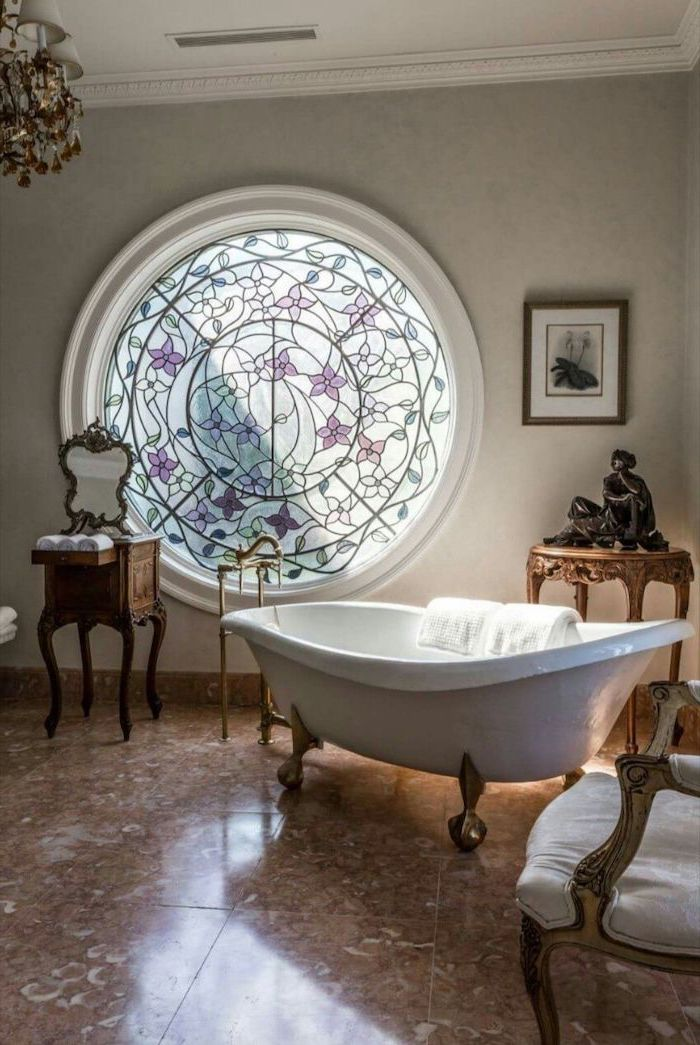 stained glass panels, bathroom with vintage bath, brown tiled floor, round window, decorated with flowers