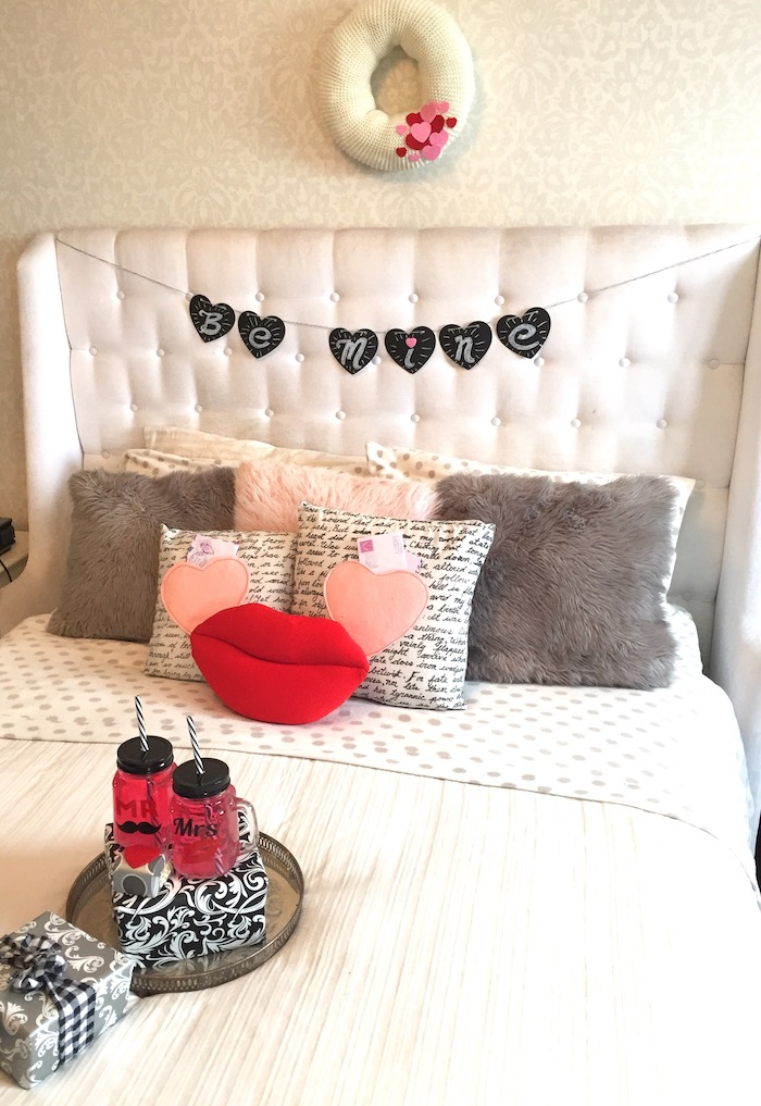 be mine banner, hanging over a bed, decorated with throw pillows, mr and mrs cups and two presents, valentine decorations ideas