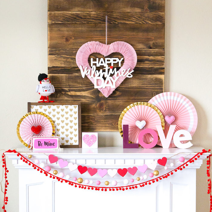 valentines day decor, pink and red decorations, heart garlands hanging over white mantel, decorations made of paper